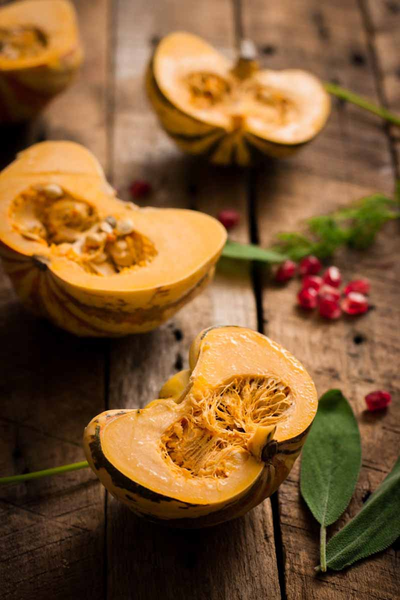 Raw sweet dumpling squash sliced into halves with selective focus on the foreground. Green herbs and fresh pomegranate arils are interspersed between the vegetable halves on a rustic wooden table top.