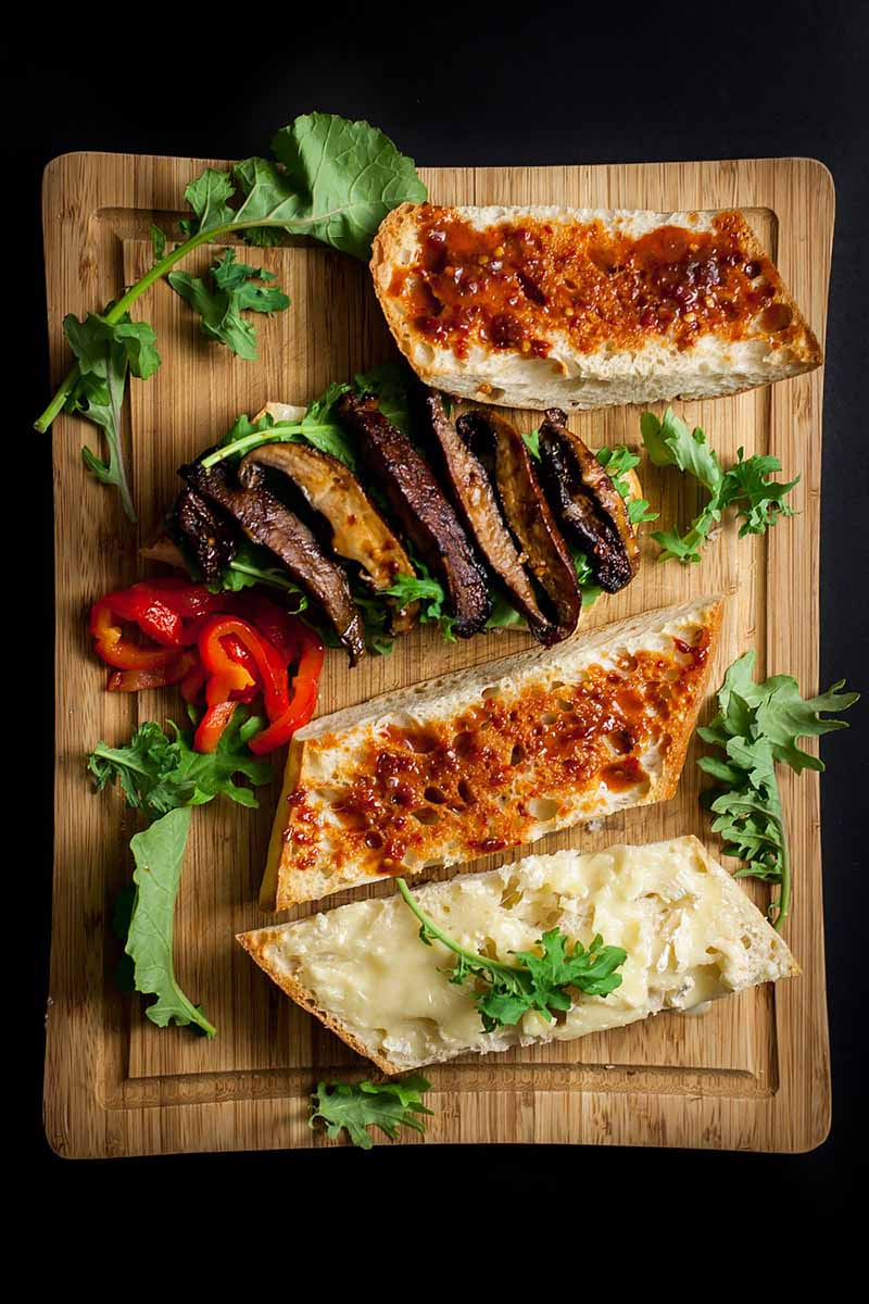 Vertical image of open-faced sandwiches with mushrooms and a red spread with fresh arugula on a wooden cutting board.