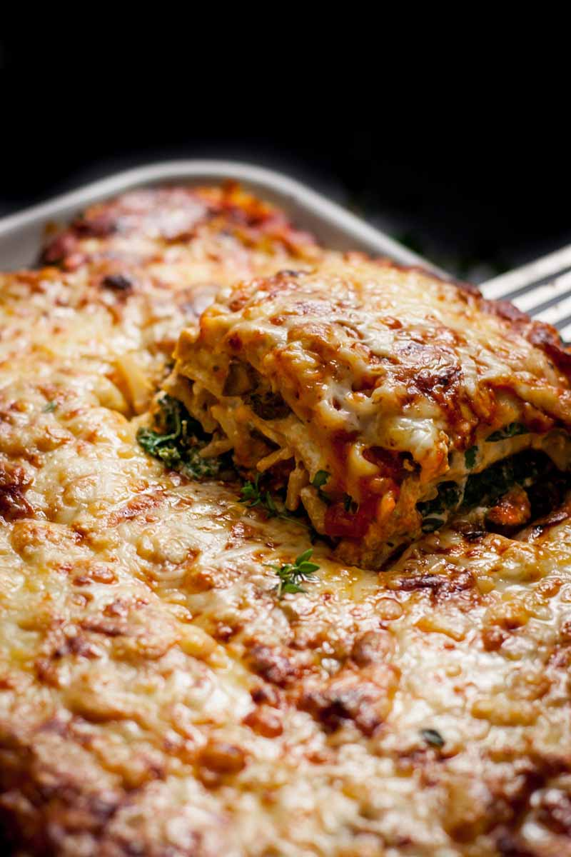 A metal spatula lifts a cube of cheesy vegetarian lasagna from a white porcelain baking dish.