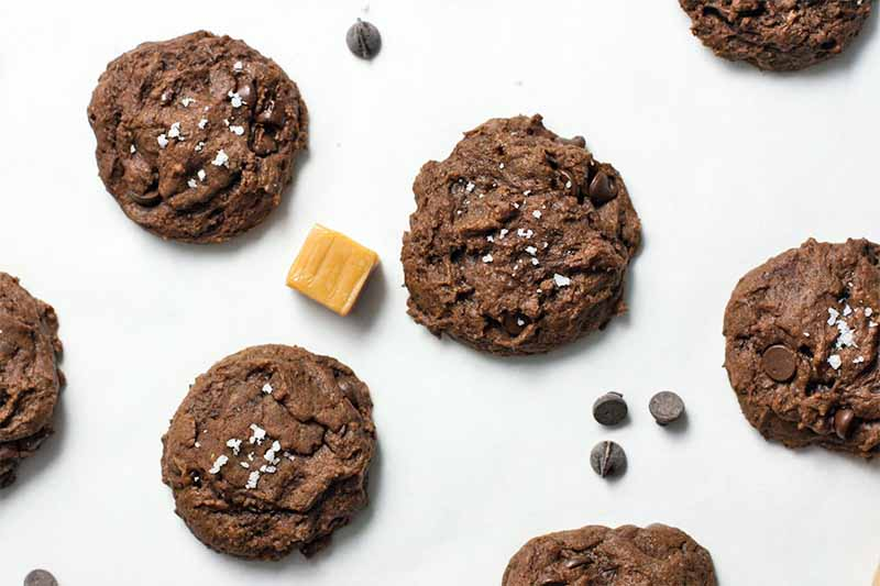 Top-down shot of chocolate chip cookies arranged in rows, with sea salt sprinkled on top, a caramel candy, and a few scattered chocolate chips, on a white parchment paper background.