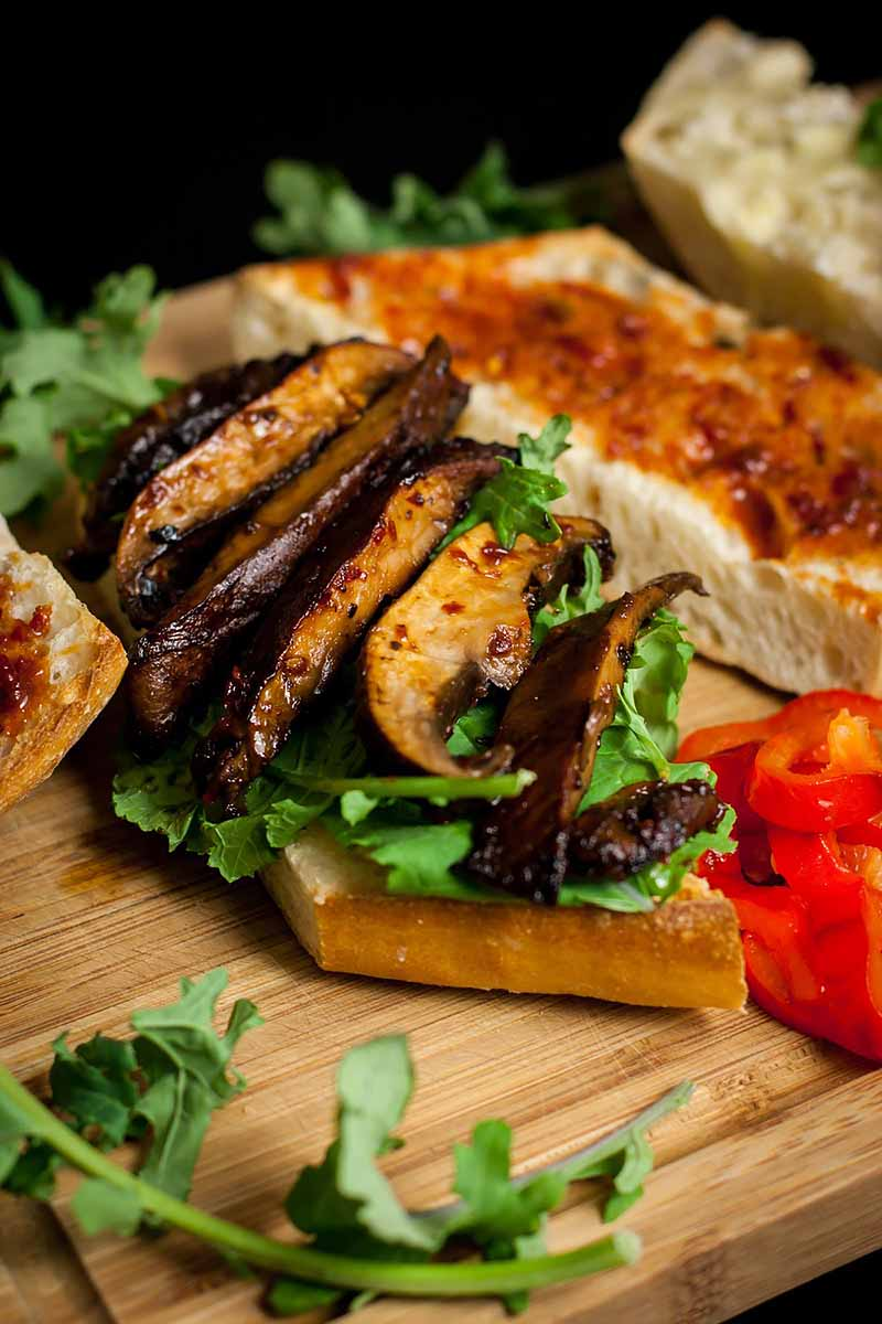 Vertical image of mushroom slices on bread with arugula and peppers.