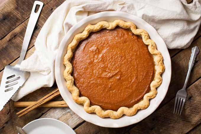 Top down view of whole vegan pumpkin pie sitting on a rustic wooden surface. A pie spatula sits to the left.