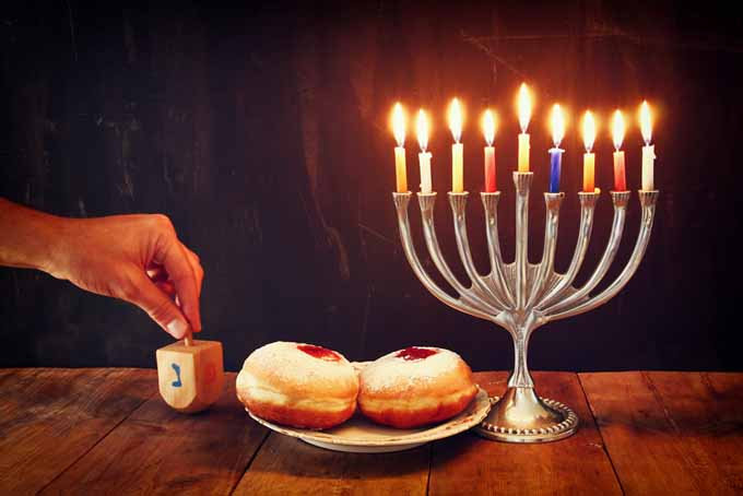 Jewish holiday Hanukkah with menorah donuts and wooden dreidels | Foodal.com