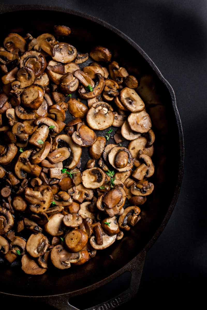 Top down view of sauteed mushrooms in a cast iron pan.
