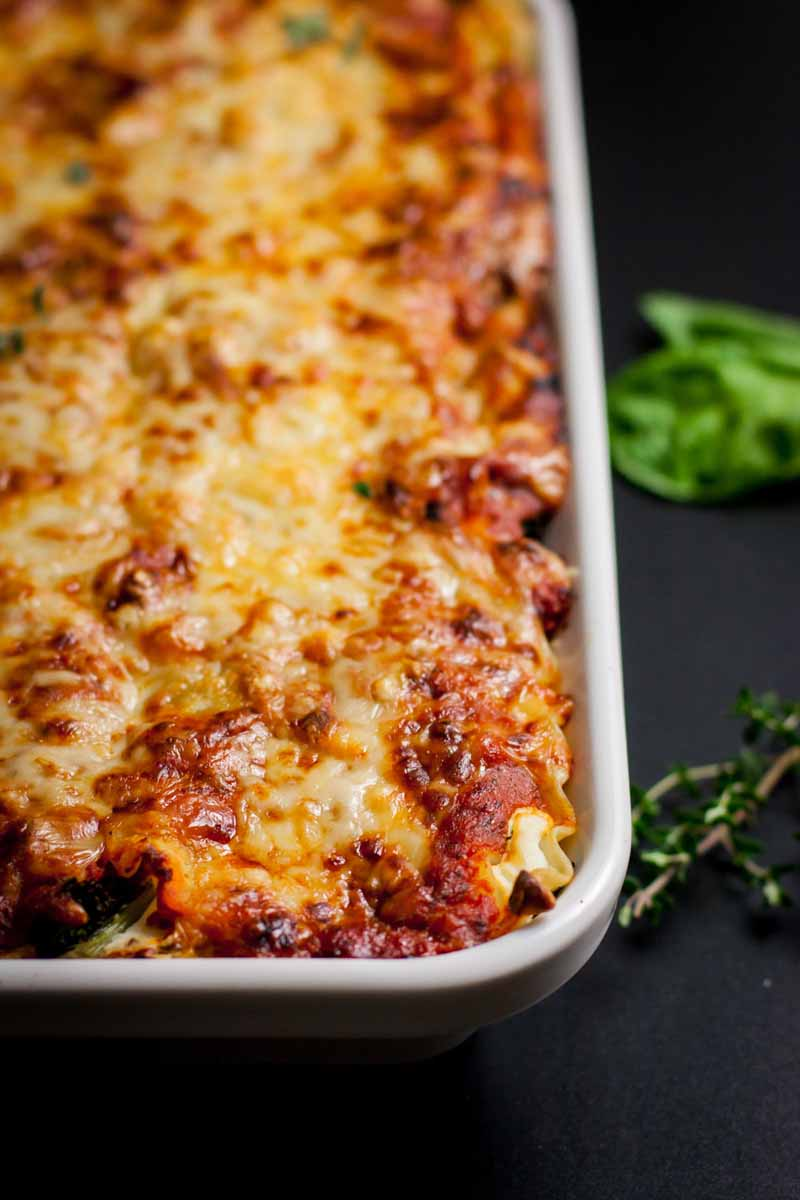 A top view of a baked cheesy lasagna in a white, porcelain casserole dish with a black background.