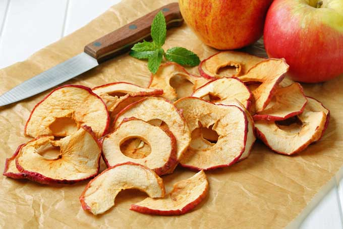 Dehydrated sliced apple rings on parchment paper | Foodal.com