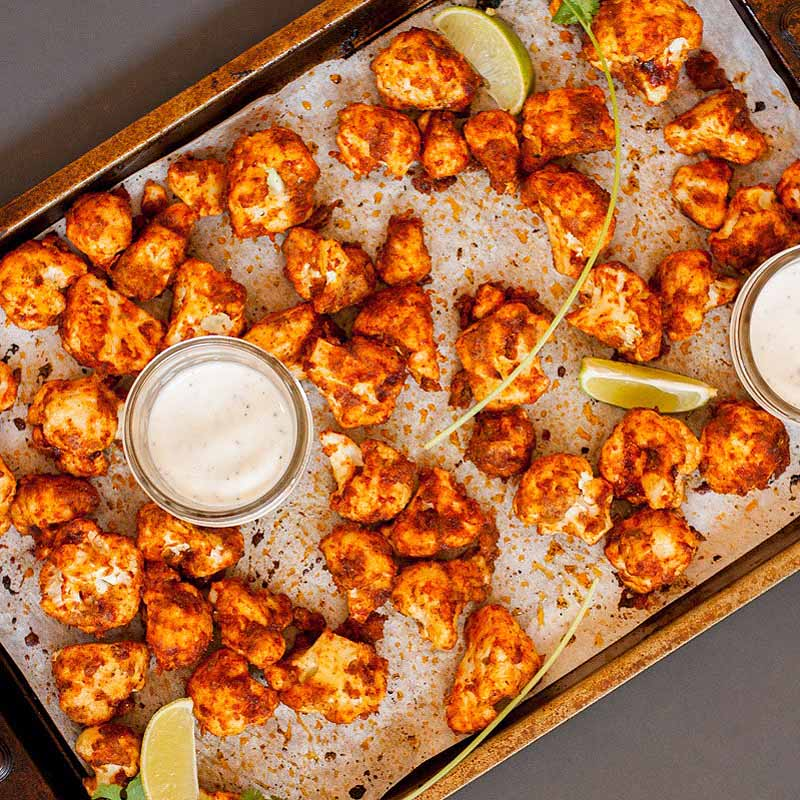 Top-down view of a rimmed baking sheet with buffalo wings made with cauliflower and flavored with hot pepper, lime, and agave syrup.