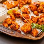 """Close up oblique view of a batch of vegan cauliflower hot wings flavored with lime and agave syrup. They """"wings"""" are sitting on a baking pan and a glass jar full of ranch dressing accompanies them."""