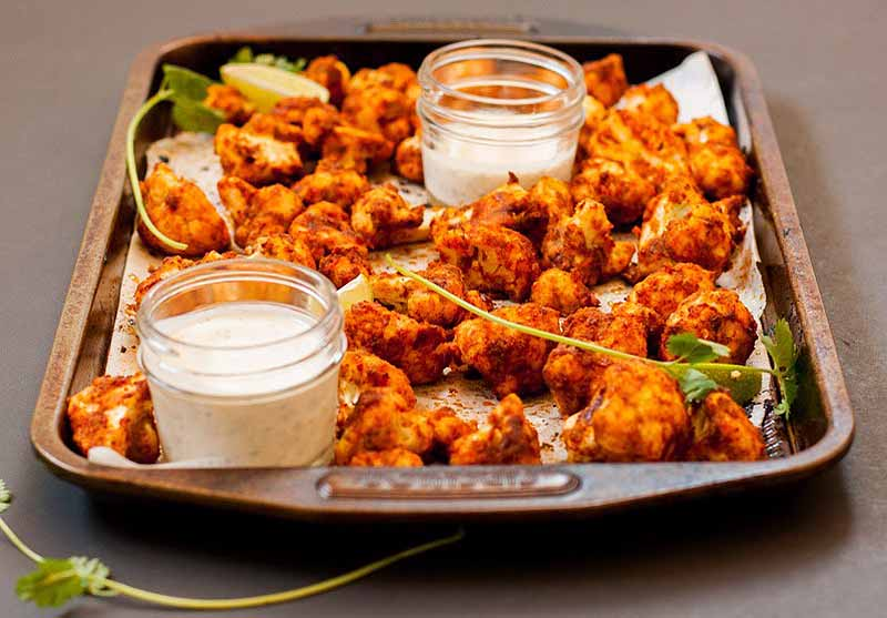 Oblique view of a baking sheet full of honey lime cauliflower hot wings with two glass containers full of ranch dressing.