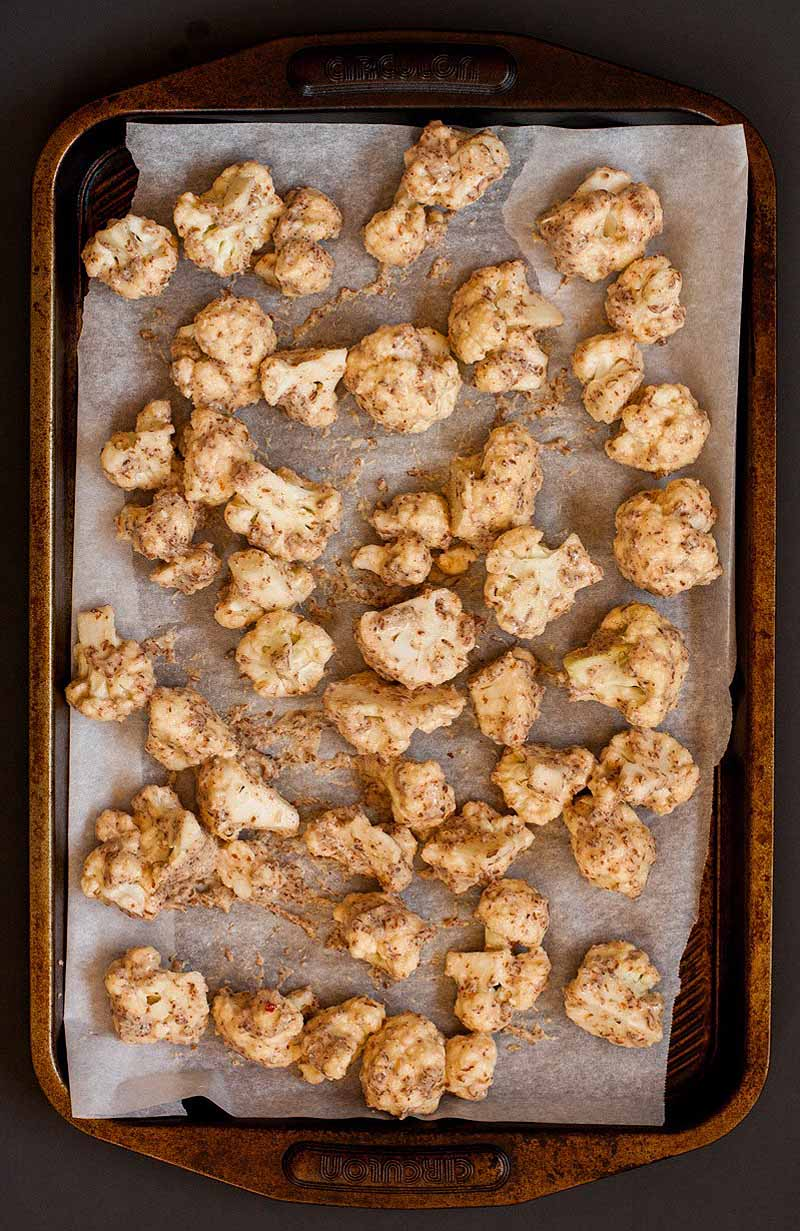 Top-down view of a baking pan full of cauliflower chunks flavored to taste similar to hot and spicy chicken wings.
