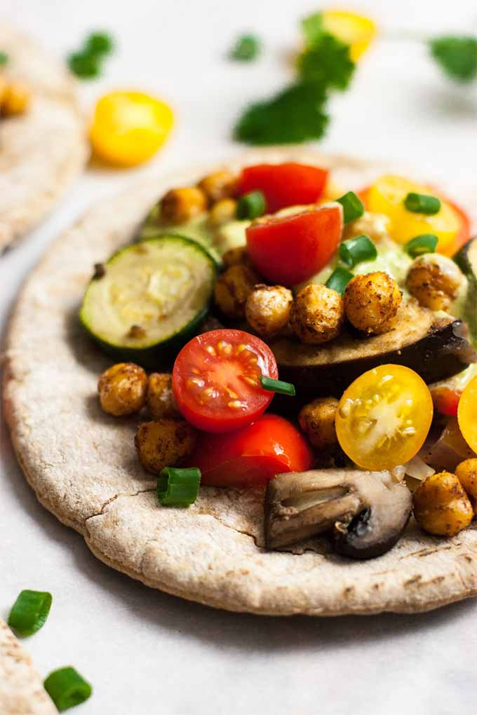 Closely cropped closeup vertical image of a whole wheat pita topped with roasted zucchini, fresh cheery tomatoes, and spicy chickpeas, on a white background with scattered herbs.