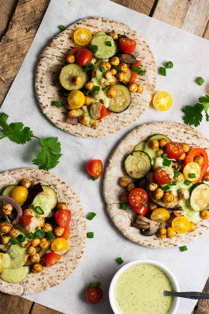 Vertical top-down shot of three whole wheat pitas topped with a mixture of roasted and fresh vegetables and chickpeas, on a piece of white parchment paper with cilantro leaves, cherry tomatoes, and a white ramekin of pale green sauce.