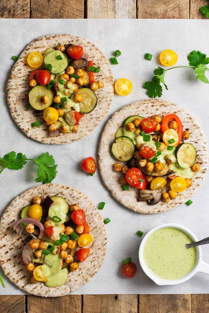 Top-down shot of three pitas topped with roasted vegetables and chickpeas, with a ramekin of pale green tahini cilantro sauce, on a white piece of parchment paper with scattered red and yellow cherry tomatoes and cilantro leaves, on a wood background.