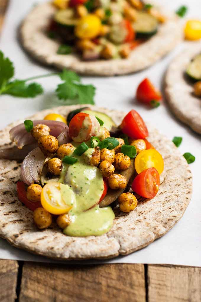 Vertical image of three pitas topped with roasted vegetables, fresh tomatoes and herbs, spicy chickpeas, and cilantro tahini sauce, on white parchment paper.