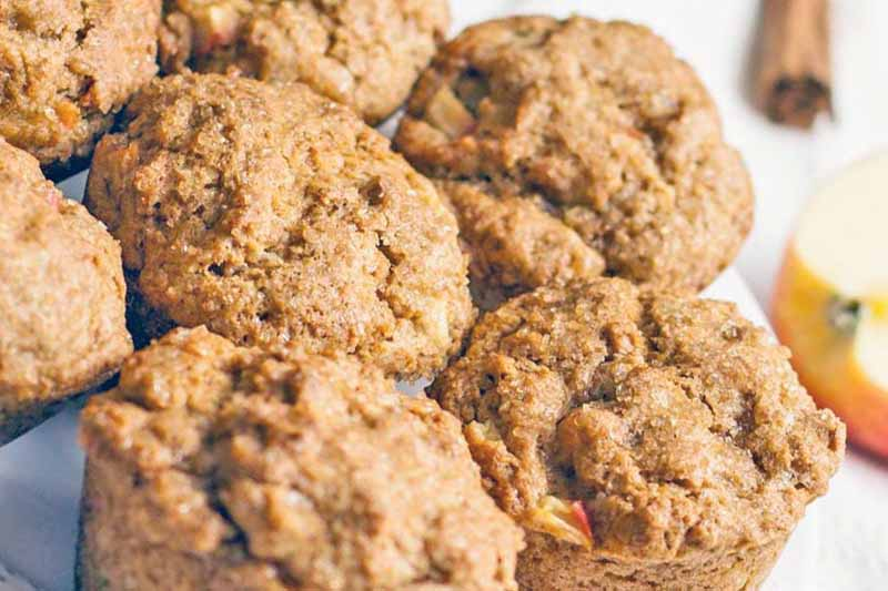 Closely cropped closeup of seven brown muffins on a plate, with a cinnamon stick and half of an apple, on a white background.