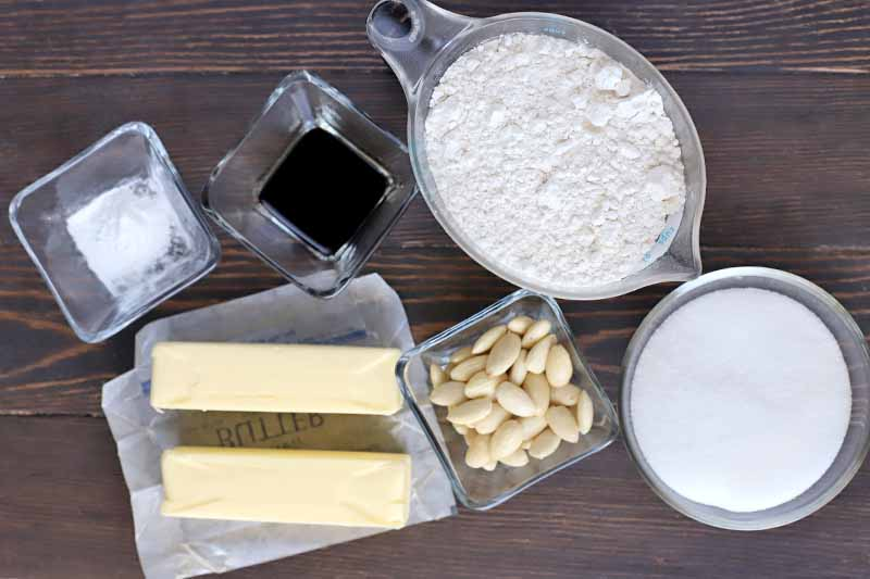 Overhead shot of a plastic pitcher of flour, a round bowl of sugar, and square glass bowls of blanched almonds, vanilla, and baking powder, beside two sicks of butter on a pieces of waxed paper, on a brown wood surface.