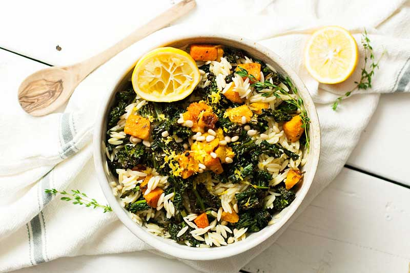 Top down view of a kale and butternut orzo past salad in white bowl on a white wooden table. A wooden spoon sits to the upper left of the bowl and an empty lemon peel to the upper right.