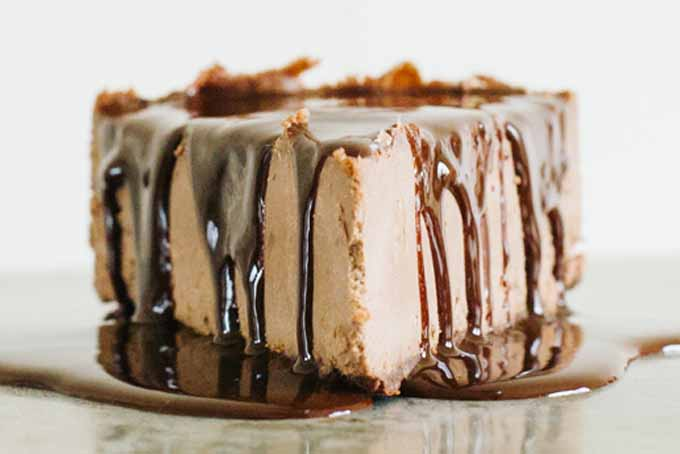 Close up of the pointy end of a slice of Cashew Cream Raw Chocolate Cheesecake showing the chocolate drizzle.
