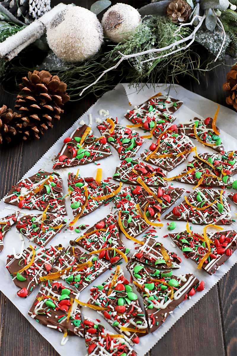 A piece of parchment paper topped with homemade chocolate bark decorated with red and green candy, on a brown wood surface with decorative pine cones, artificial greenery, and white baubles.