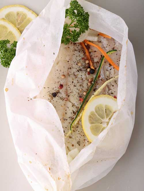 Fish being prepared for steaming en papillote | Foodal.com