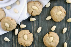 Brown butter cookies and blanched almonds scattered on a brown wood surface that's partially covered with a white cloth.
