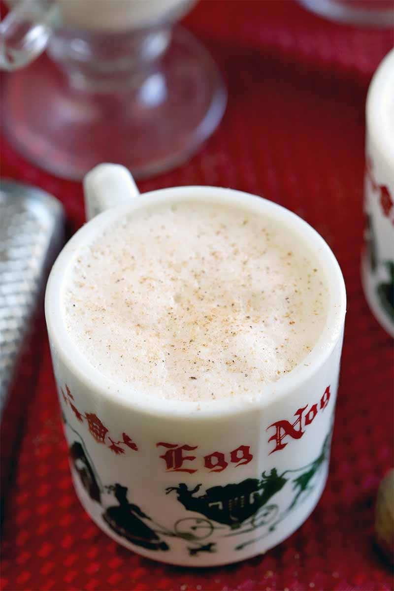 Closeup oblique shot of a white mug with red and green holiday decorations that is filled with eggnog topped with nutmeg in the foreground, with another ceramic mug and a glass beside a metal grater, on a red cloth.