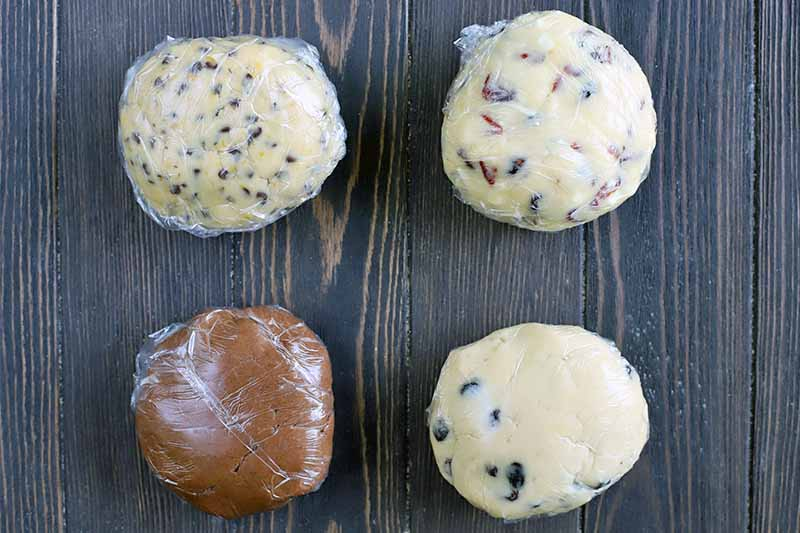 Four balls of various types of cookie dough, wrapped tightly in plastic, on a dark brown wood surface.
