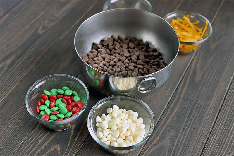 A stainless steel stand mixer bowl of chocolate chips with smaller glass bowls of green and red M&M's, white chocolate chips, candied orange peel, and another bowl whose contents are masked by the mixing bowl, on a dark brown wood table.