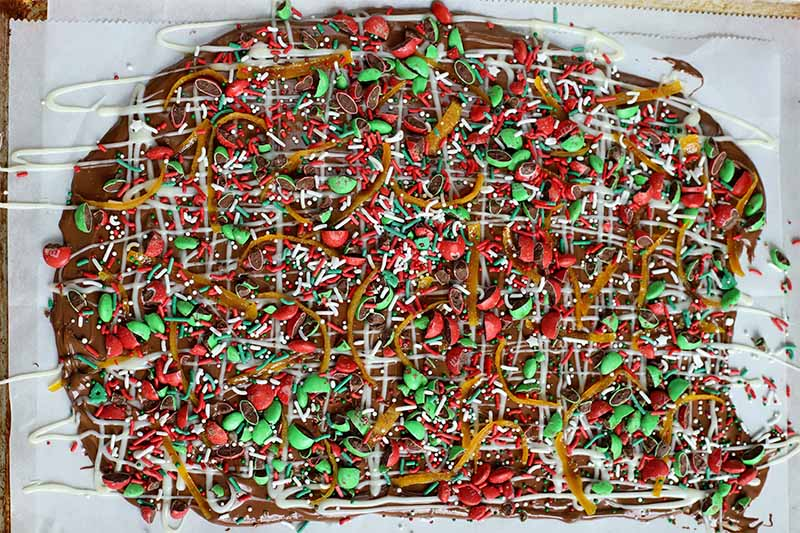 Melted chocolate is spread in a thin layer on parchment paper and topped with a drizzle of the white variety, thin pieces of candied orange peel, and chopped green and red M&M's.