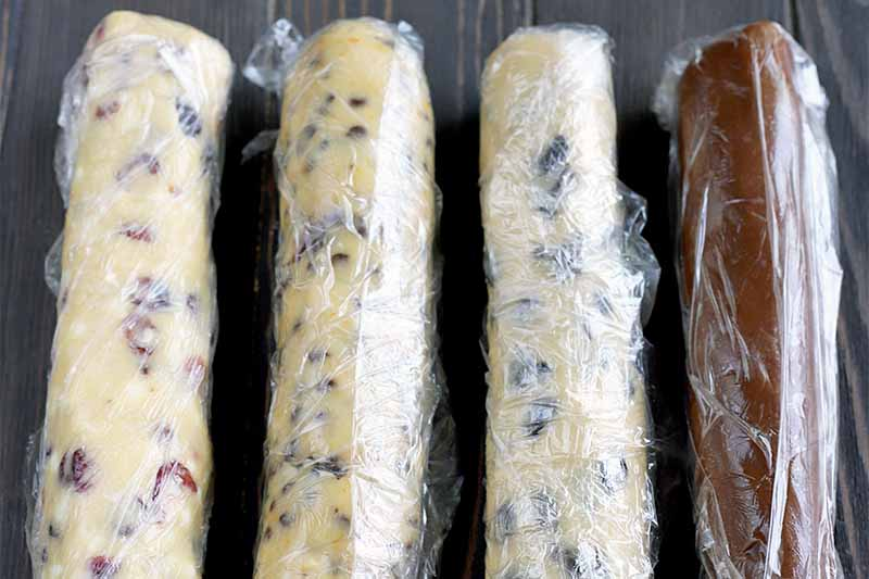 Four logs of cookie dough with various flavorings and add-ins, wrapped in plastic wrap, on a brown wood surface.