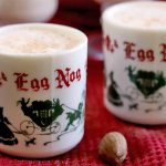 Two decorative red, green, and white holiday-themed mugs of eggnog, with a whole nutmeg and metal grater on a red kitchen towel that is spread over a dark brown wood table.