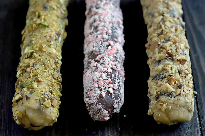 Three logs of cookie dough rolled in crushed nuts and candy, on a brown wood surface.