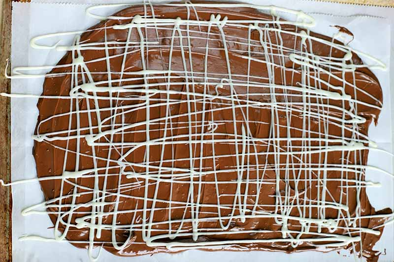 Melted chocolate is spread in a thin layer across the surface of a piece of parchment paper, with the white type drizzled on top.