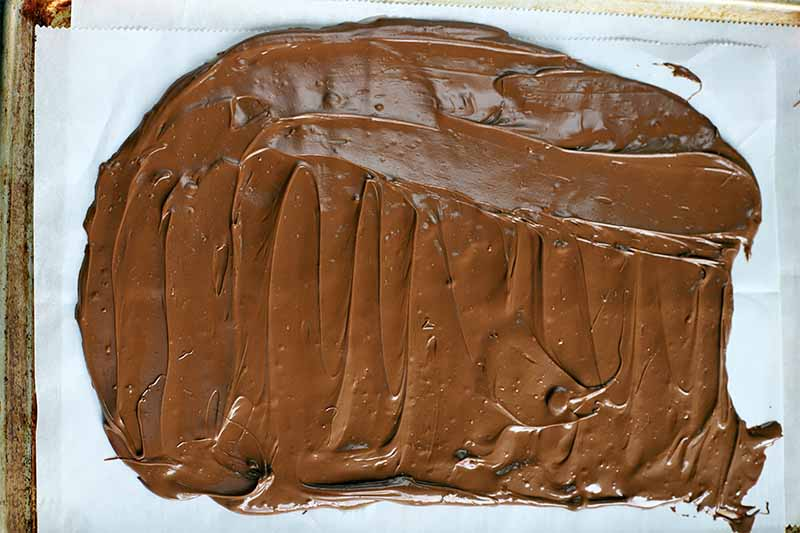 Overhead shot of melted chocolate spread in a thin layer on a rectangular piece of white parchment paper.