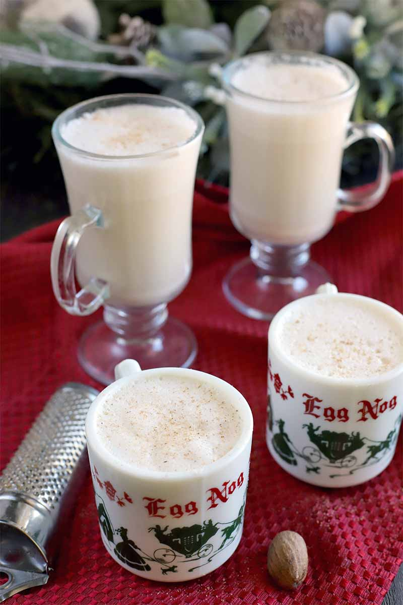 Two glass and two ceramic holiday mugs of homemade eggnog, with a whole nutmeg and a metal grater on a red kitchen towel that is spread over a dark brown wood surface, with decorative artificial greenery in teh background.