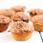 Oblique shot of seven blueberry muffins with crumble topping shot with selective focus, on a white wood background.