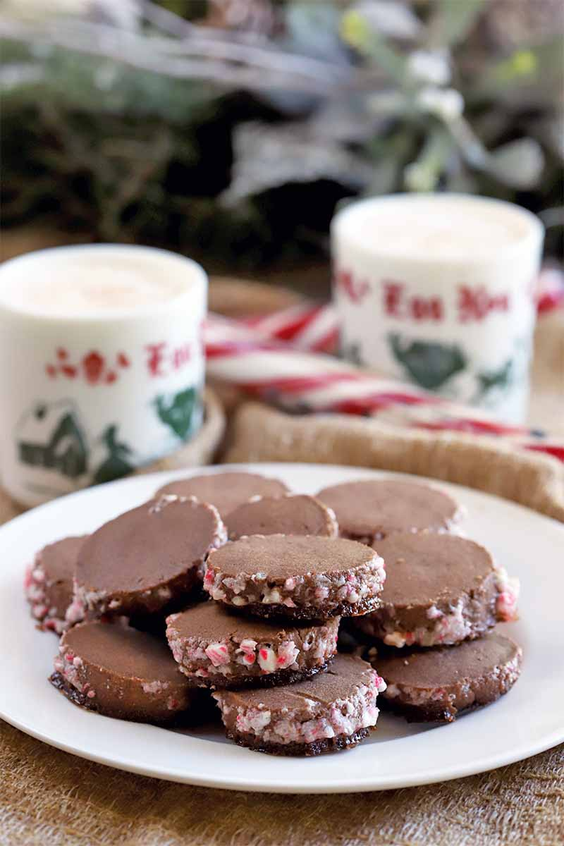 A white plate of chocolate butter cookies that have been rolled in crushed candy canes is in the foreground, with mugs of eggnog and more candy in soft focus on a piece of burlap in the background.
