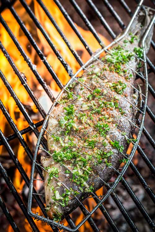 Trout on the BBQ inside of a grilling basket | Foodal.com