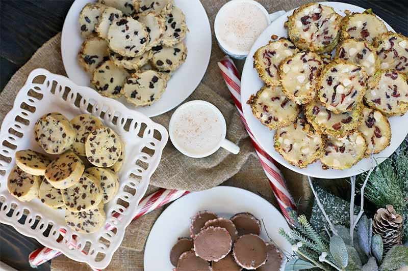Top-down shot of four white plates of homemade cookies flavored with various mix-ins, on a piece of burlap cloth on top of a dark brown wood surface, with decorative artificial greenery, candy canes, and peppermint sticks, and two mugs of eggnog sprinkled with ground nutmeg.