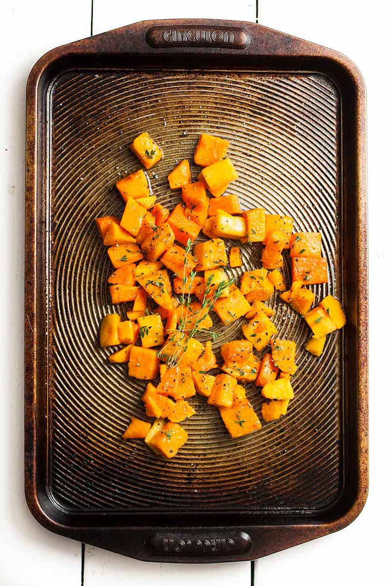 Top down view of roasted butternut squash cut into chunks on a baking sheet.