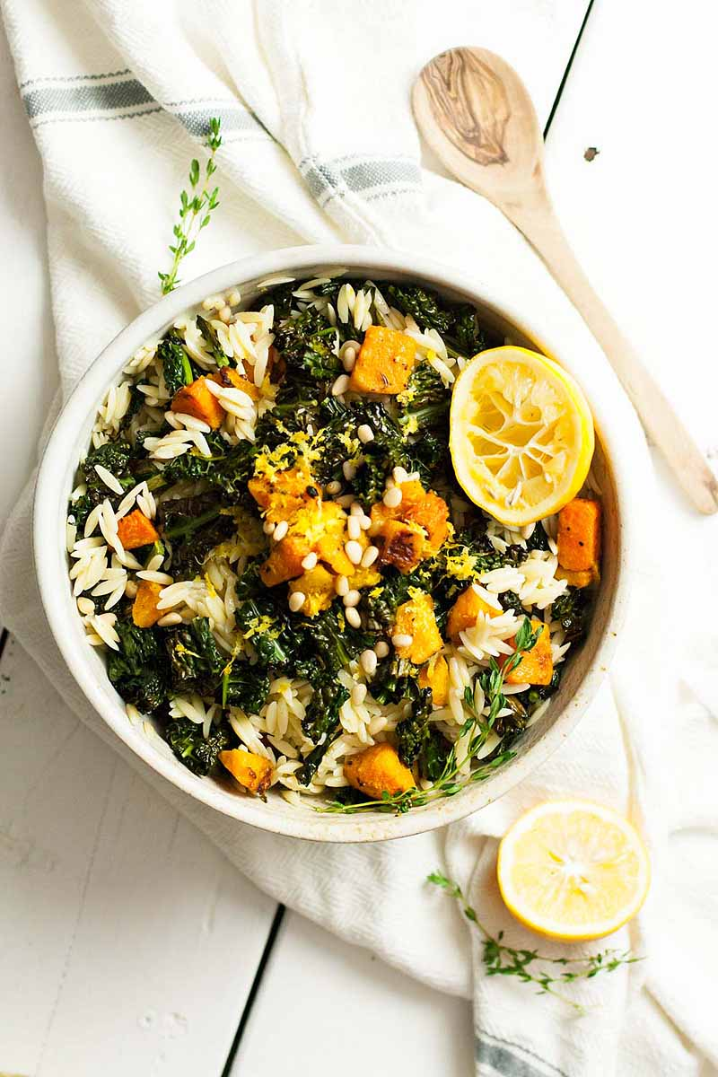 Top down view of a bowl of butternut squash and kale pasta salad sitting on a white kitchen towel and a white painted wooden table.