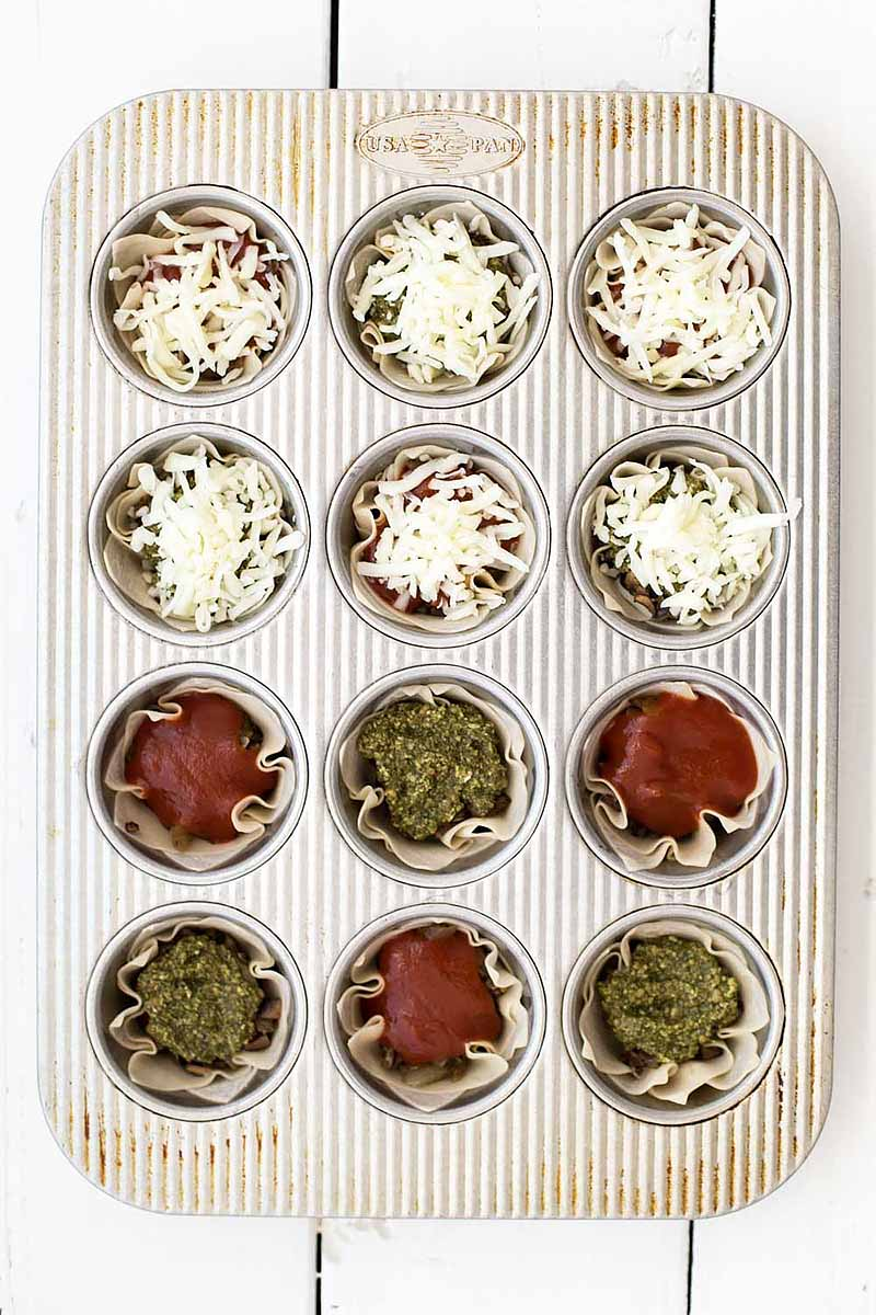Vertical top-down image of unbaked lasagna cups in a muffin tin with assorted garnishes.
