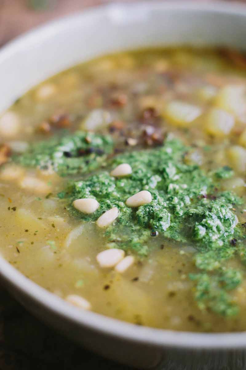 Vertical close-up image of a bowl of stew topped with green herbs.