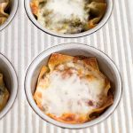 Horizontal image of pasta and cheese in a muffin baking tin.