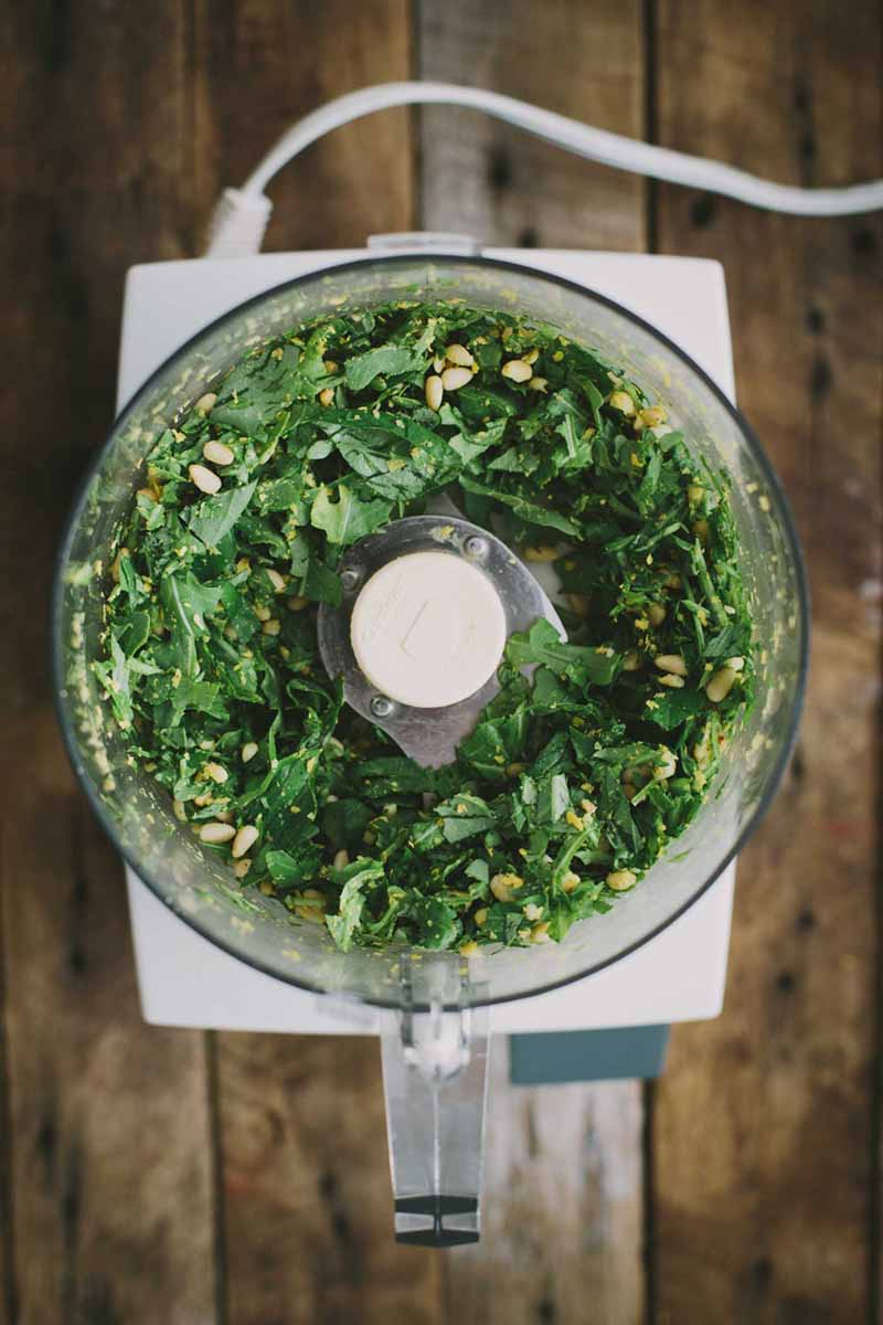 Vertical image of pesto ingredients in a food processor on a wooden table.