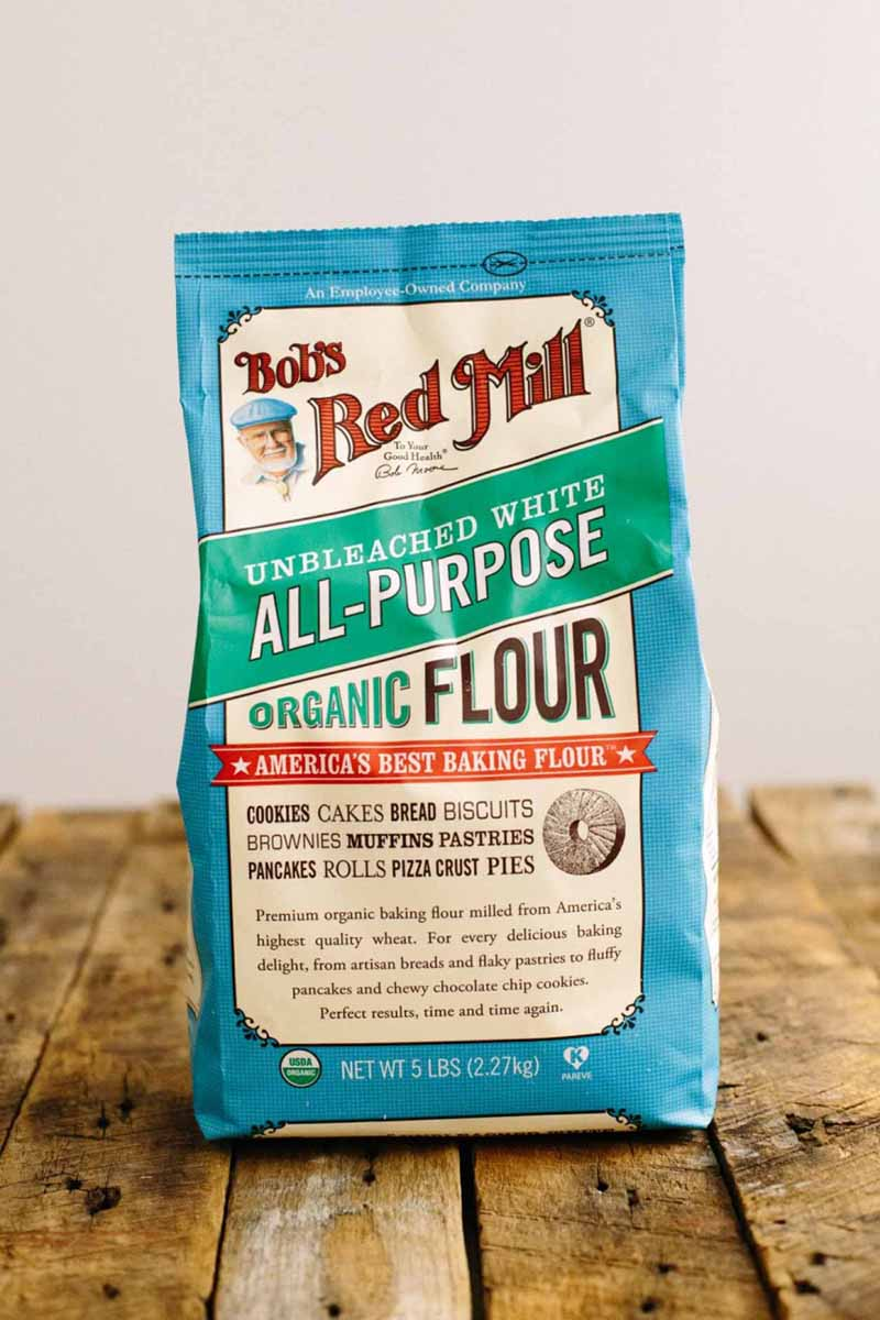 A bag of Bob's Red Mill Organic All-Purpose Flour sitting on a rustic wooden surface.