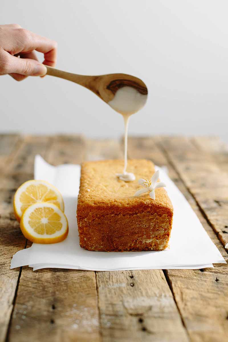 A human hand dribbles glaze with a wooden spoon over the top of a vegan lemon pound cake.