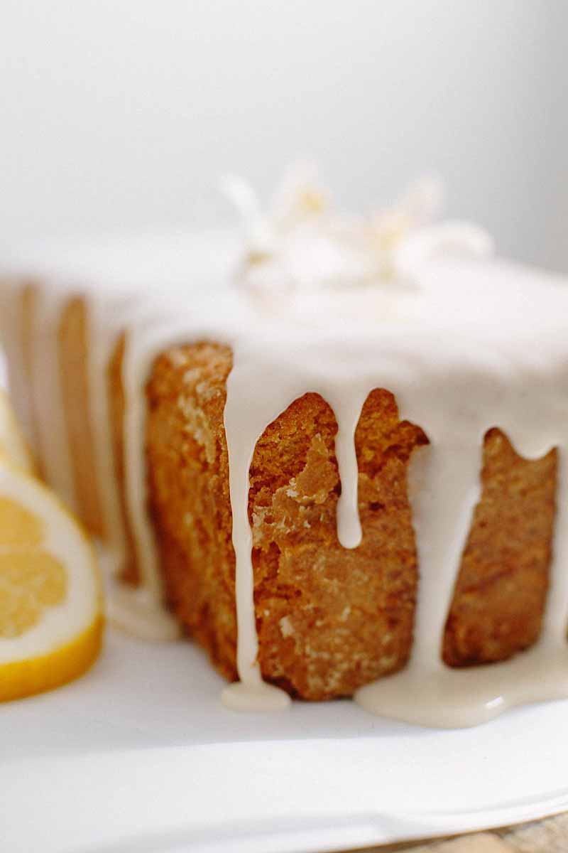 Close up of the corner of glazed lemon pound cake showing details of the frosting dribbling over the edges.