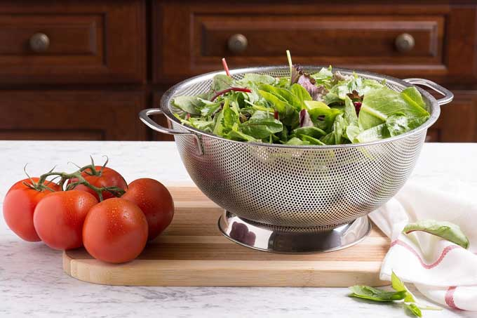Bellemain Micro-perforated Stainless Steel 5-quart Colander with lettuce and tomatoes.