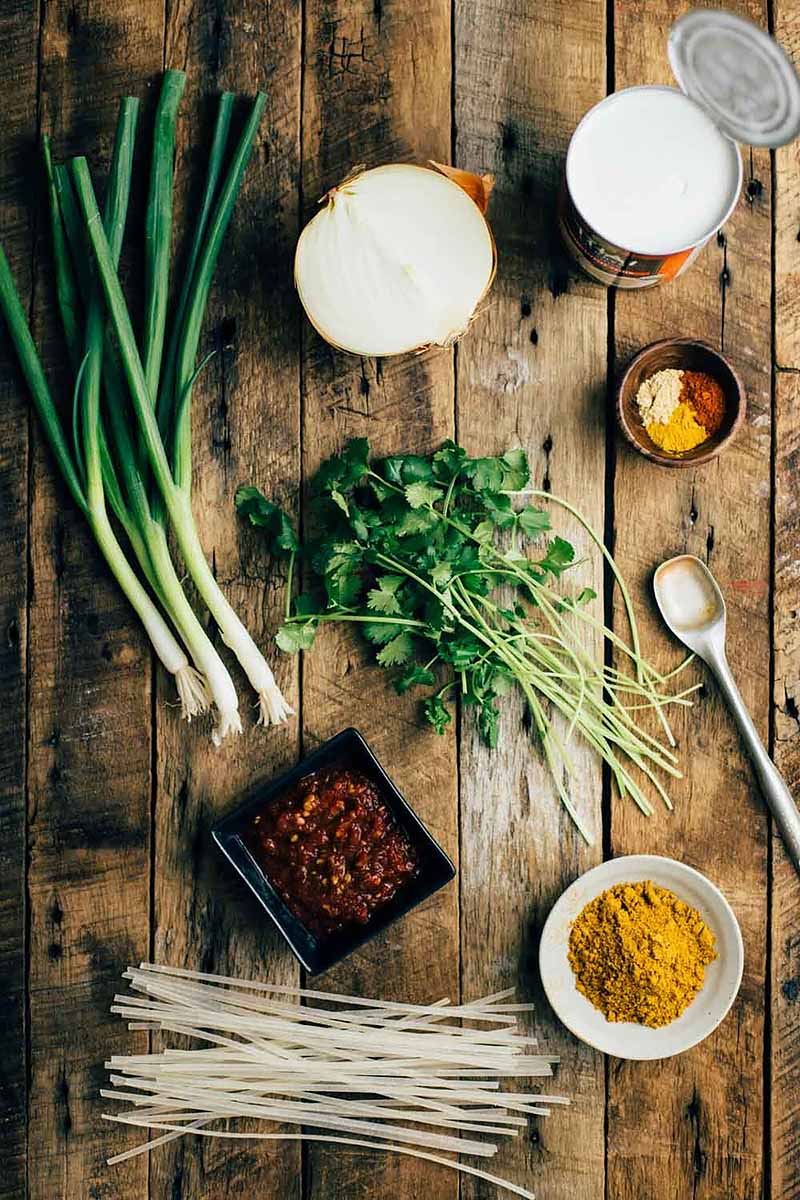 Vertical image of ingredients for curry on a wooden surface.